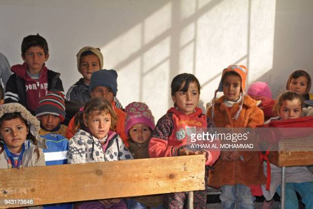 Syrian children sit on a classroom at school in the village of AlShamatiyah on the ourskirts of Deir Ezzor on February 7 2018 Since a Syrian...