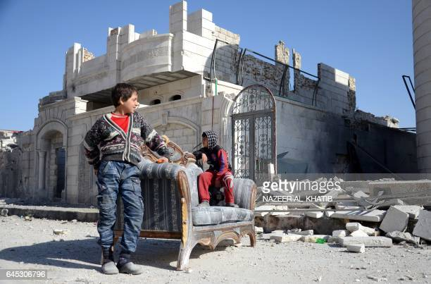 TOPSHOT Syrian children sit on a sofa outside a destroyed building in the northwestern border town of alBab on February 25 2017 after Turkishbacked...