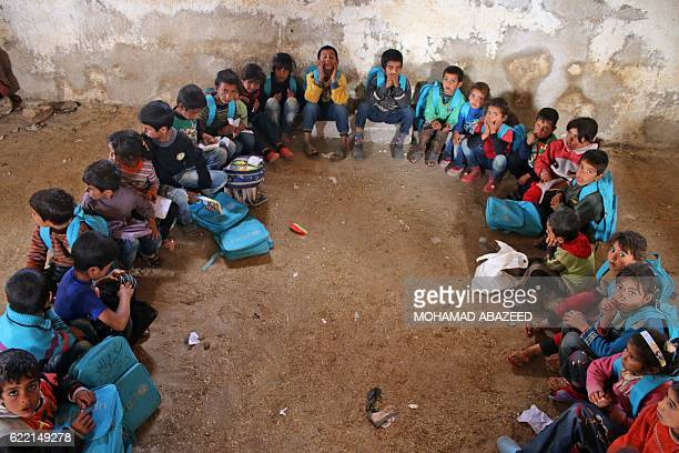 Syrian children sit on the floor in a barn that has been converted into a makeshift school to teach internally displaced children from areas under...