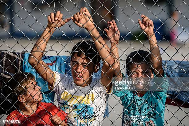 Syrian children stand behind a fence at a refugee camp in the Kilis district of Gaziantep southeastern Turkey on October 23 2016 France's foreign...