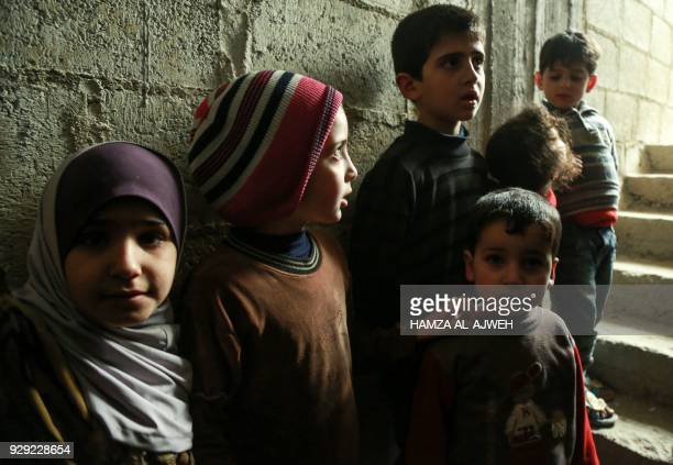Syrian children stand by a wall at the entrance of a basement being used as a makeshift bomb shelter in the rebelheld town of Douma in the Eastern...