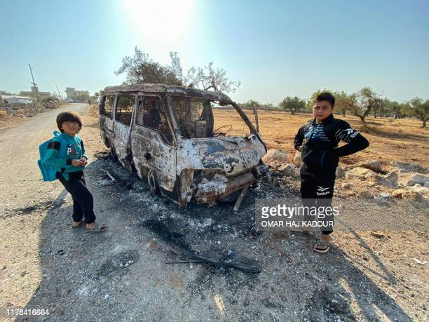 Syrian children stand next to a burnt vehicle on October 27, 2019 near the site where helicopter gunfire reportedly killed nine people near the...
