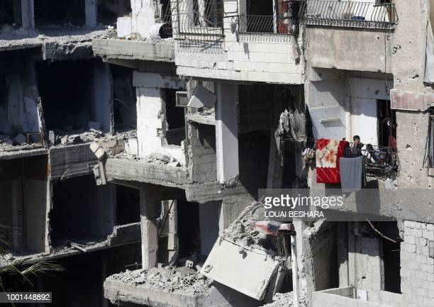 Syrian children stand on a balcony of a destroyed building in Harasta on the outskirts of the Syrian capital Damascus on July 15 2018 After a...