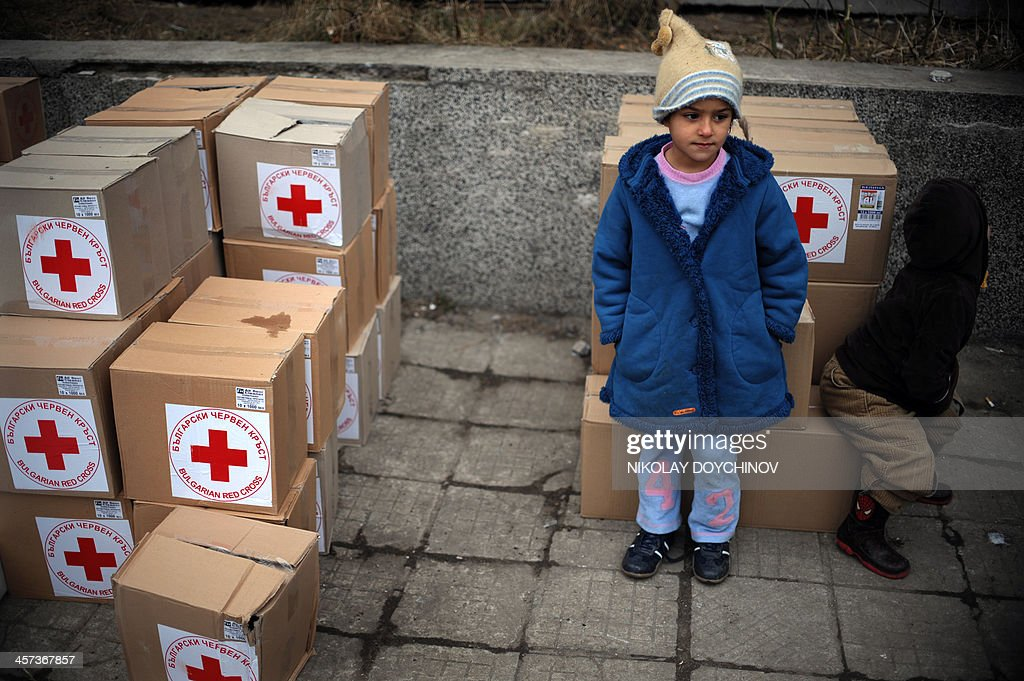 Syrian children stands next to aid boxes from the Bulgarian Red Cross during an aid distribution of food, clothes and blankets at a refugee center in Sofia on December 17, 2013. Over 11,100 refugees, most of them Syrians, have entered Bulgaria illegally this year, crossing the border with Turkey. The number of Syrian refugees in the Middle East will nearly double over the next year to exceed four million, the United Nations said on Monday as it launched its appeal for funds.
