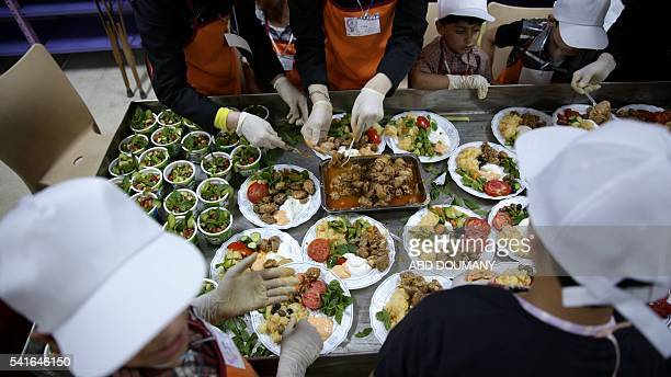 Syrian children take part in a cooking competition to prepare iftar meals during the Muslim holy fasting month of Ramadan in the rebelheld town of...