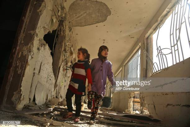 Syrian children tour their damaged school on November 9, 2017 in the besieged rebel-held Eastern Ghouta town of Saqba, on the outskirts of the Syrian...
