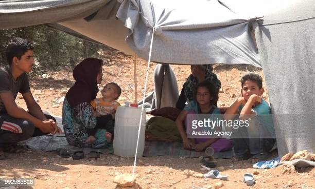 Syrian children wait at the border areas near Jordan after they fled from the ongoing military operations by Bashar alAssad regime and its allies in...