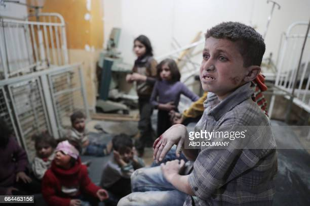 TOPSHOT Syrian children wait to receive treatment at a makeshift clinic following reported air strikes by government forces in the rebelheld town of...