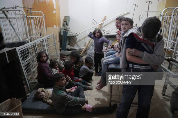 Syrian children wait to receive treatment at a makeshift clinic following reported air strikes by government forces in the rebelheld town of Douma on...