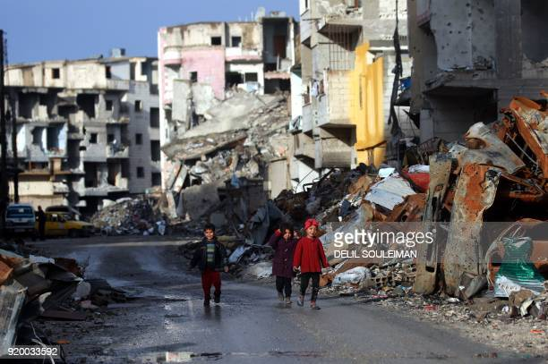 TOPSHOT Syrian children walk along a destroyed street in Raqa the former de facto capital of the Islamic State group on February 18 2018 / AFP PHOTO...