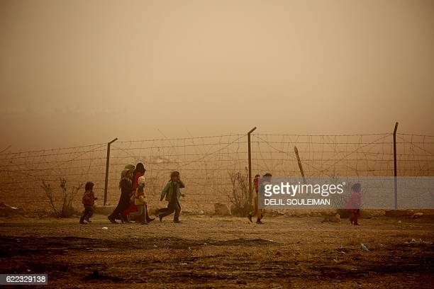 Syrian children walk around the camp grounds during a sandstorm at a temporary refugee camp in the village of Ain Issa, housing people who fled...