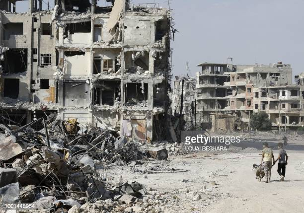 Syrian children walk by the rubble of destroyed buildings in Harasta on the outskirt of the capital Damascus on July 15 2018 After a blistering...
