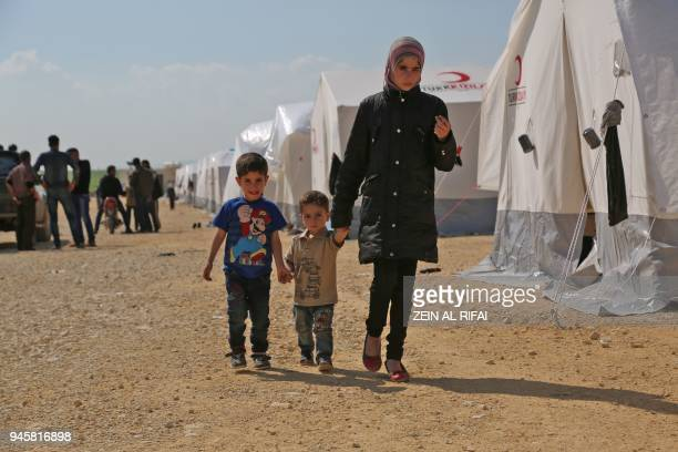 Syrian children walk in a camp for displaced Syrians from the former rebel bastion of Douma in alBil east of the rebelheld town of Azaz in northern...