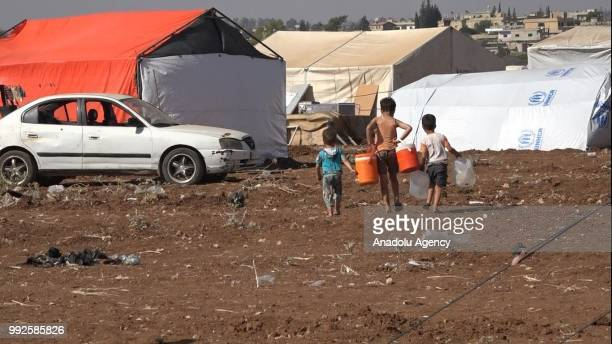 Syrian children walk on a field at the border areas near Jordan after they fled from the ongoing military operations by Bashar alAssad regime and its...