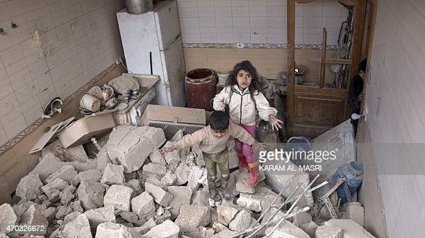 Syrian children walk on rubble after their building partially collapsed following a reported airstrike by government forces on a rebel held area of...