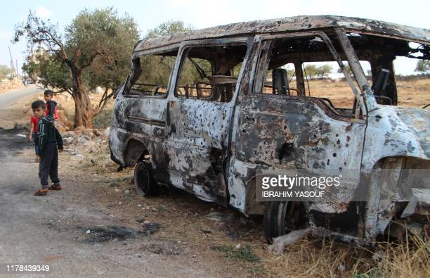 Syrian children walk past a damaged van at the site of helicopter gunfire which reportedly killed nine people near the northwestern Syrian village of...