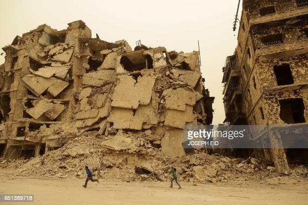 Syrian children walk past destruction in the once rebel-held Kastal al-Harami neighbourhood in Aleppo during a sandstorm on March 10, 2017. / AFP...