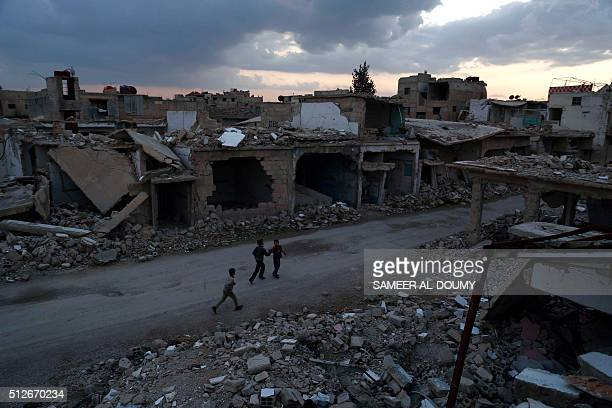 Syrian children walk past heavily damaged buildings in the rebelheld town of Douma on the eastern edges of the capital Damascus on February 27 on the...