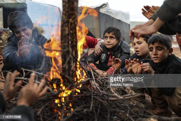 Syrian children warm up near a fire at muddy ground at Yavru Fida Camp with 90 tents in Idlib Syria on January 7 2020 Syrian families fled from Assad...
