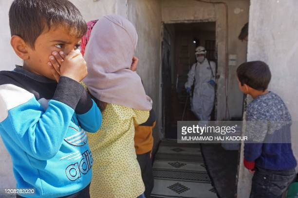 Syrian children watch a member of the Syrian civil defence, known as the White Helmets, disinfecting a former school building currently inhabited by...