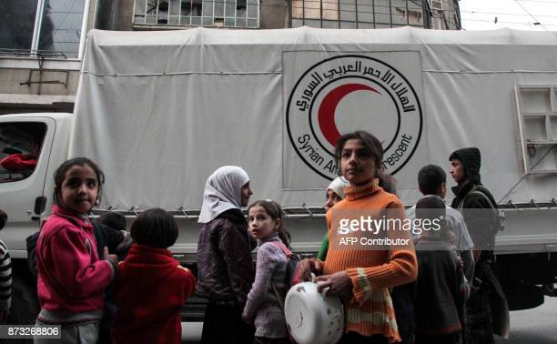 Syrian children watch as packages humanitarian relief provided by the International Committee of the Red Cross in a joint operation with the UN are...
