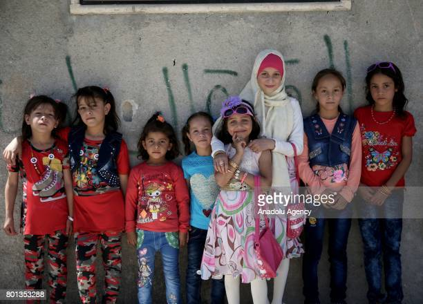 Syrian children wearing Eid alFitr clothes pose for a photo during the Eid alFitr holiday in Jarabulus district of Aleppo Syria on July 26 2017...