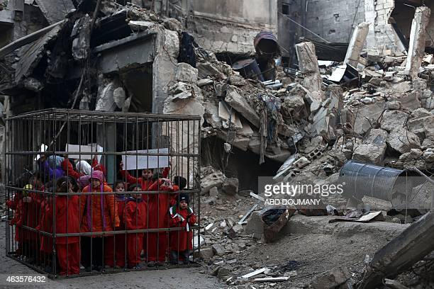 Syrian children wearing orange jumpsuits stand inside a cage on February 15 2015 placed near the debris of a building destroyed in bombardment by...