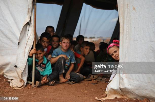 Syrian children who fled with their families from the northern countryside of Hama are pictured in a classoom at the makeshift school of Zuhur...