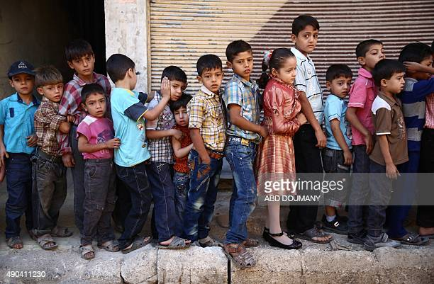 Syrian children who lost one or both of their parents in Syria's ongoing conflict line up to attend a party organised for them by the local NGO Douma...