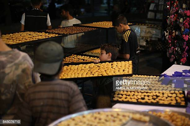Syrian children work at a pastry shop selling traditional sweets in the rebelheld town of Saqba on the eastern outskirts of the capital Damascus late...