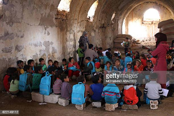 Syrian children write during class a barn that has been converted into a makeshift school to teach internally displaced children from areas under...
