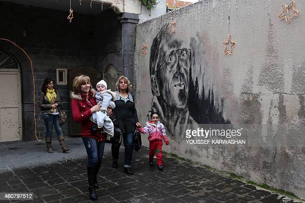 Syrian Christian women walk past a mural depicting Father Frans van der Lugt who was shot dead by an unknown attacker on April 7 as they leave the...