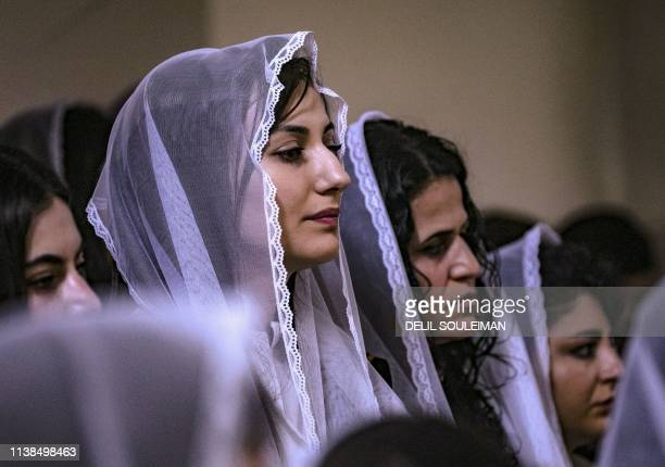 Syrian Christians pray during Palm Sunday celebrations at the Syriac Orthodox Church of the Virgin Mary in the northeastern Syrian Kurdish-controlled...