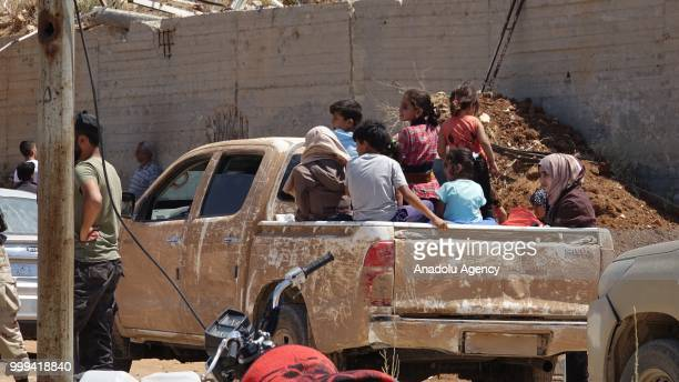 Syrian citizens are seen on a lorry as they leave Syrias southwestern Daraa province with the 1st convoy on July 15, 2018. The convoy of 15 buses...