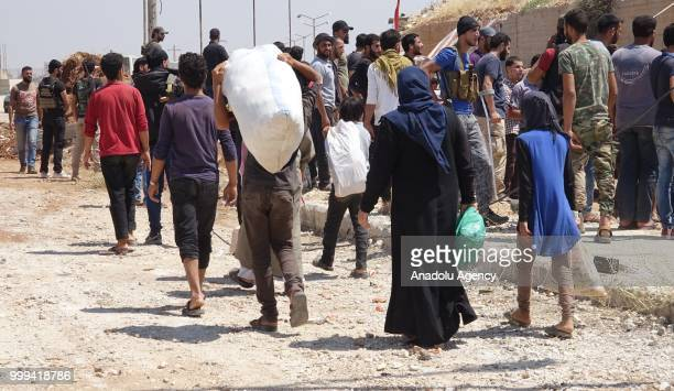 Syrian citizens are seen with their belongings as they wait to leave Syrias southwestern Daraa province with the 1st convoy on July 15 2018 The...