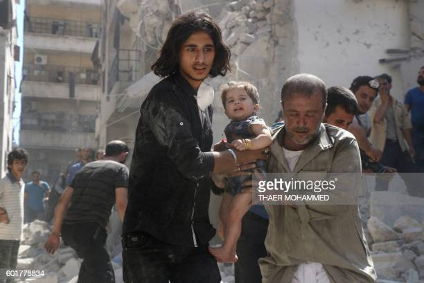 A Syrian civil defence member and a volunteer carry a little girl rescued from under the rubble of destroyed buildings following a reported airstrike...