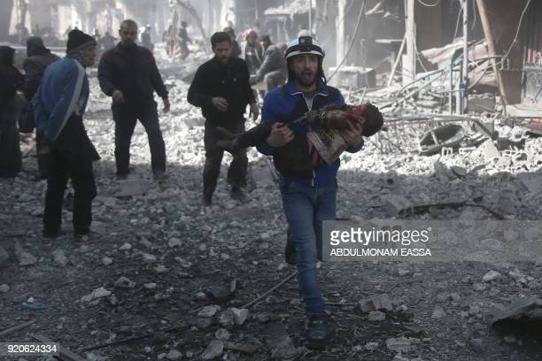 Syrian civil defence member carries an injured child rescued from between the rubble of buildings following government bombing in the rebelheld town...