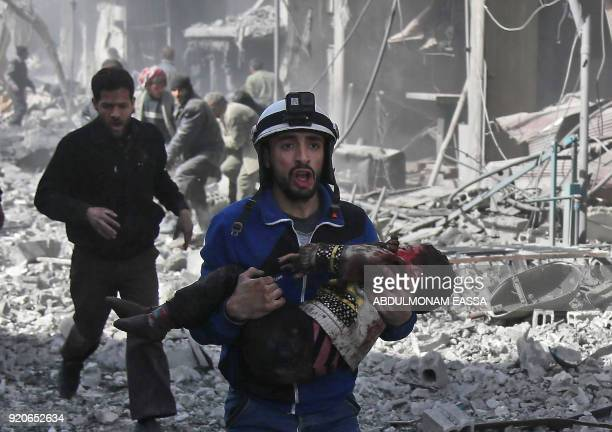A Syrian civil defence member carries an injured child rescued from between the rubble of buildings following government bombing in the rebelheld...