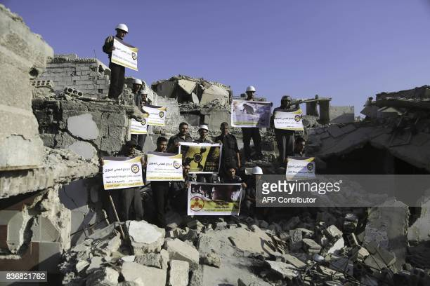 Syrian Civil Defence members also known as the White Helmets stand in protest on August 22 2017 on the rubble of buildings in Zamalka near Syria's...