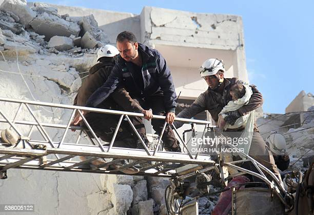 TOPSHOT Syrian Civil Defence members evacuate a toddler from the rubble of buildings destroyed following Russian air strikes a day earlier on the...