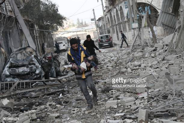 Syrian civil defence volunteer carries a little girl who was rescued from the rubble following reported bombardment by Syrian and Russian forces in...