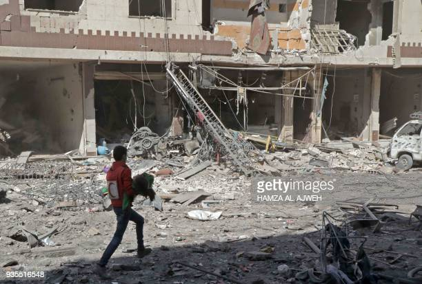 Syrian civil defence volunteer carries an injured girl following Syrian government air strikes on the Eastern Ghouta rebel-held enclave of Douma, on...