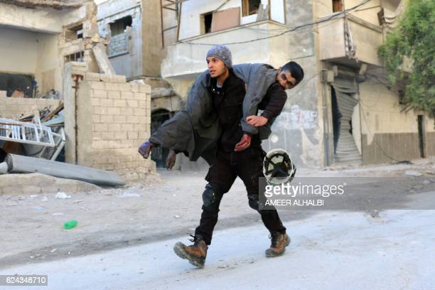 Syrian civil defence volunteer known as the White Helmets carries an injured man on November 19 2016 following a reported air strike on Aleppo's...