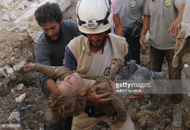 A Syrian civil defence volunteer known as the White Helmets holds the body of a child after he was pulled from the rubble following a government...