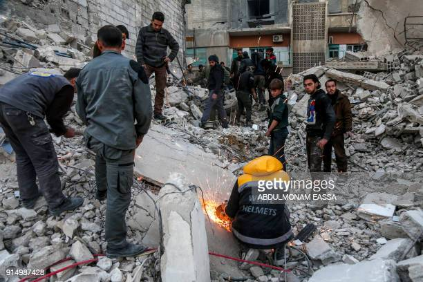 Syrian civil defence volunteers and other civilians attempt to remove rubble from the site of a collapsed building to rescue victims following...