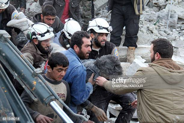 TOPSHOT Syrian civil defence volunteers carry a wounded man following a reported airstrike by government forces in the Syrian town of Binnish on the...
