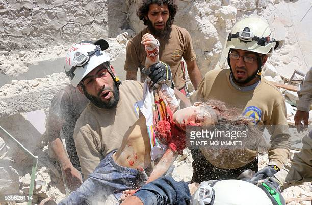 TOPSHOT Syrian civil defence volunteers carry the body of a girl dug out from the rubble following a reported attack by Syrian government forces on...