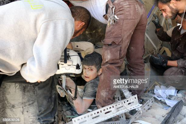 TOPSHOT Syrian civil defence volunteers help a boy out of the rubble following a reported attack by Syrian government forces on May 30 in the Tariq...