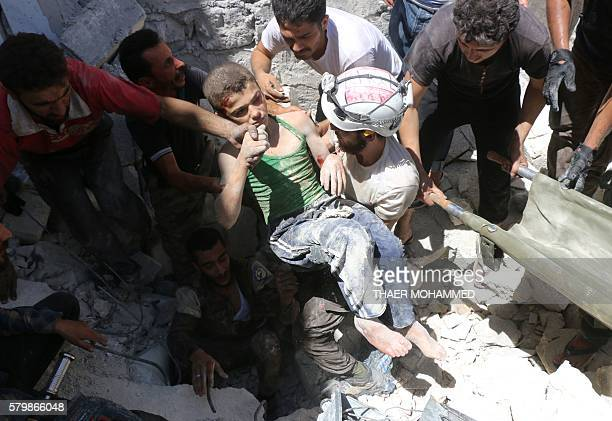 TOPSHOT Syrian civil defence volunteers known as the White Helmets carry a young boy after they dug him out from under the rubble of buildings...