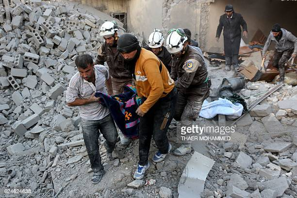 Syrian civil defence volunteers known as the White Helmets evacuate a victim from the rubble of a building following reported airstrikes on Aleppo's...